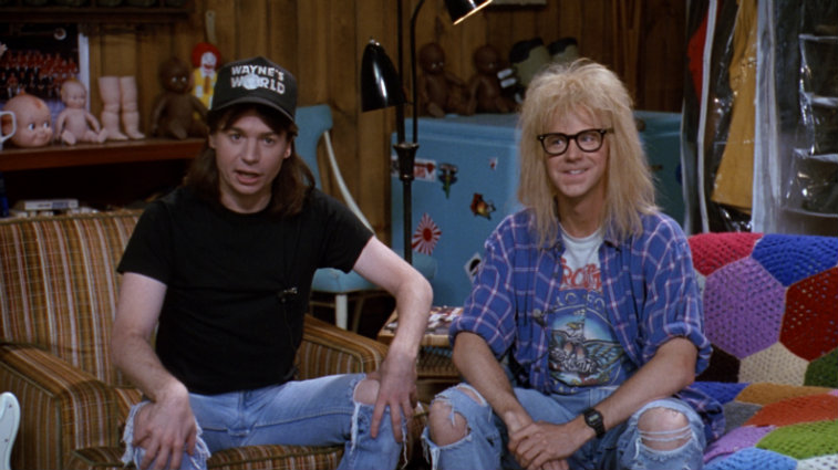 Mike Myers wears a Wayne's World hat while sitting next to Dana Carvey in a scene from Wayne's World