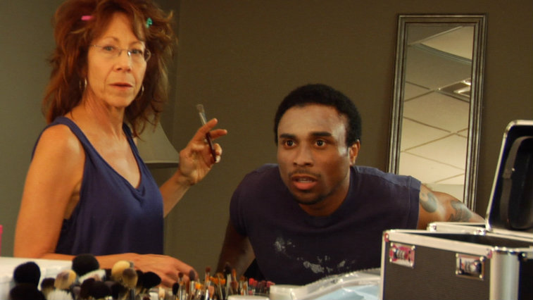 Mindy Sterling does Richard Pierre-Louis' makeup as he looks in a mirror