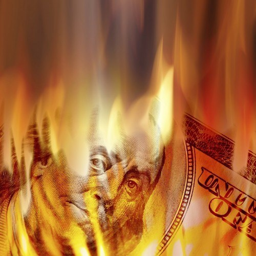 a dollar bill burning in fire