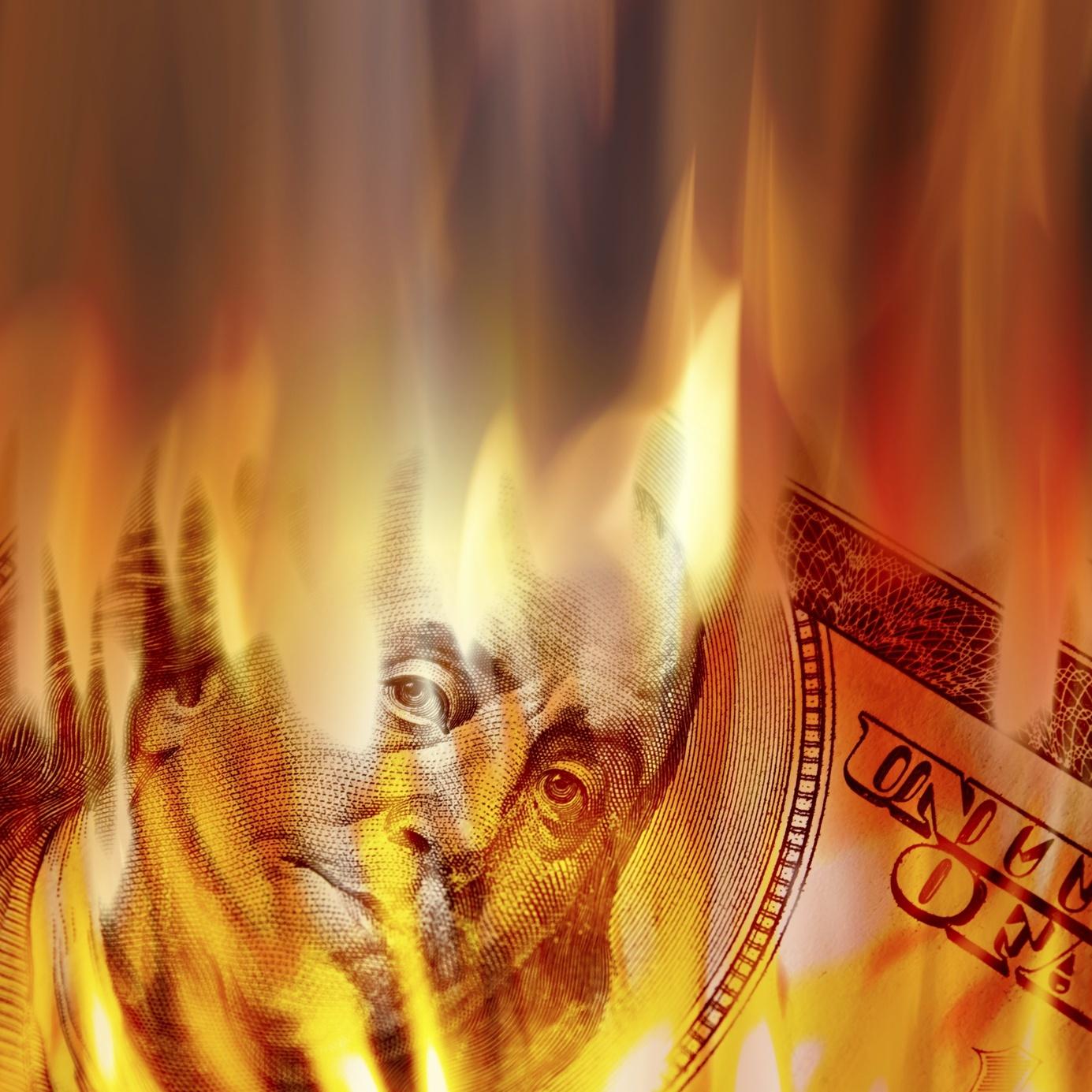a dollar bill burning in fire