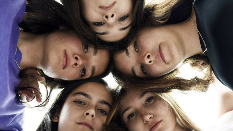 Five girls with their heads together and solemn expressions