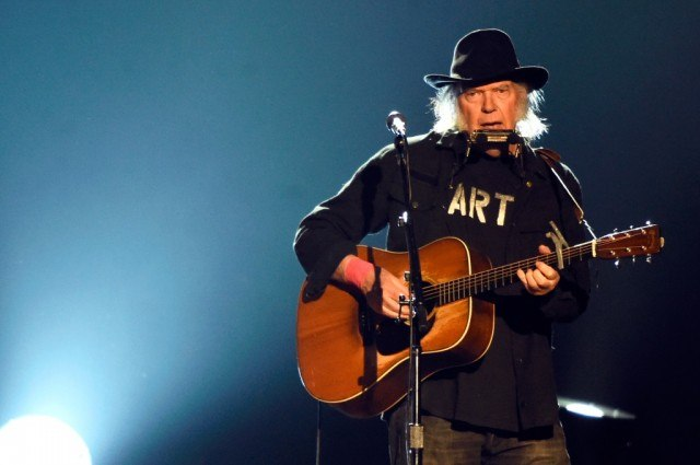 Neil Young performs in front of a microphone behind a brown acoustic guitar and a harmonica.