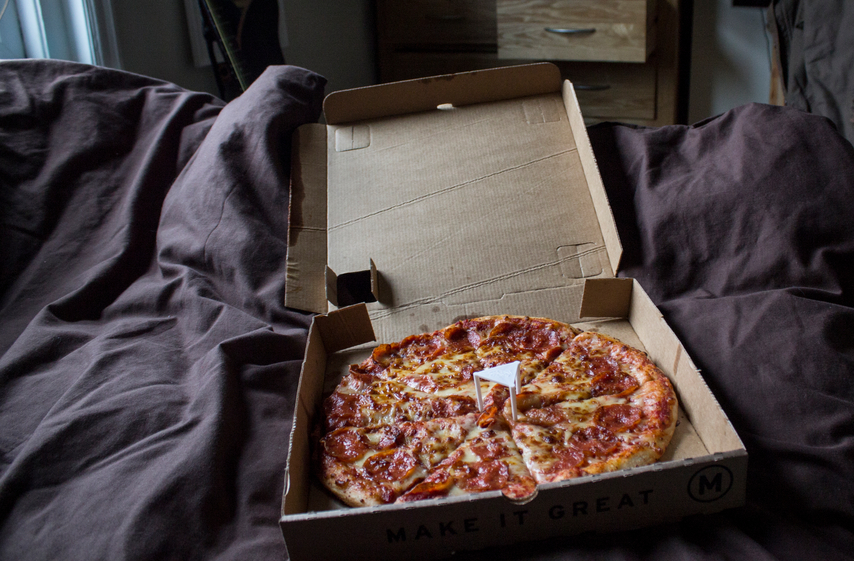 Pizza in a box on bed