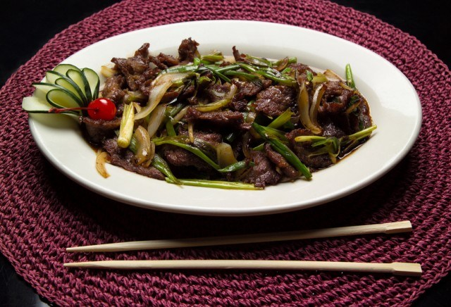 Mongolian beef on a rimmed white plate