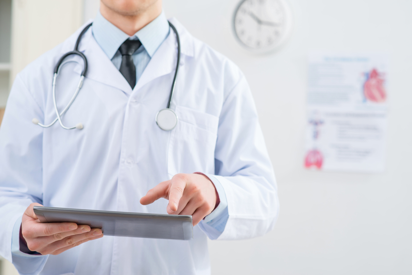 Doctor holding a tablet , perhaps a cancer or diabetes diagnosis