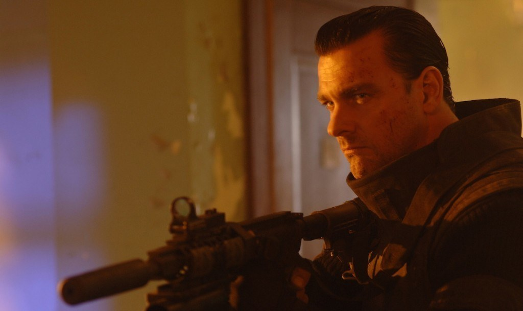 Ray Stevenson as Frank Castle aiming a rifle in Punisher: War Zone