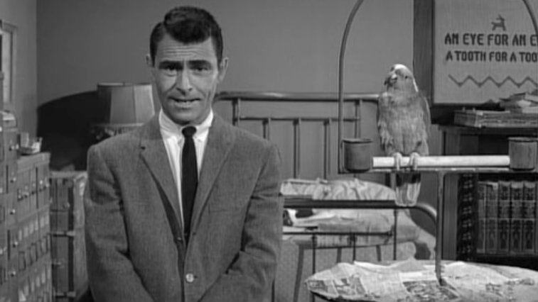 Rod Serling in black and white standing in front of a bed in The Twilight Zone