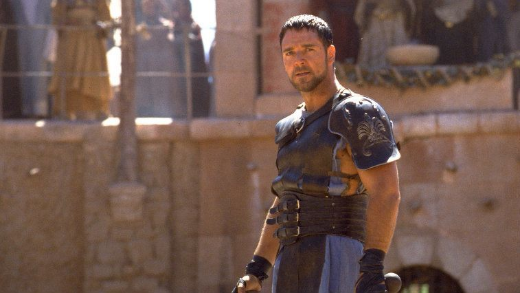 Russell Crowe in Gladiator stands in the area, in his armor, holding a sword and sheild.