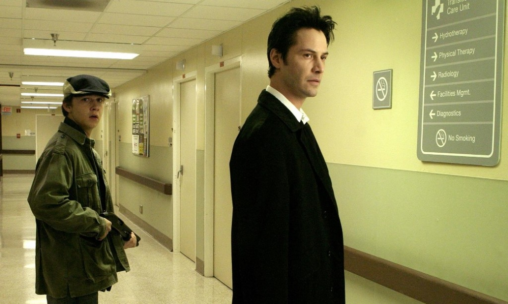 Shia LaBeouf holds a gun standing in a hallway with Keanu Reeves in Constantine
