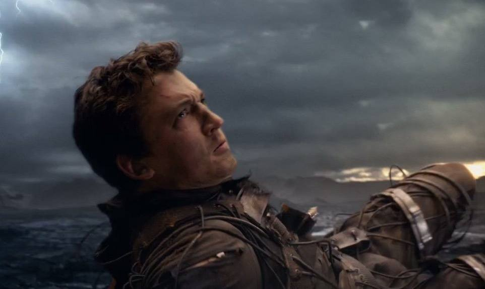 Miles Teller in Fantastic Four, laying on the ground and looking defiantly up to the right of the frame