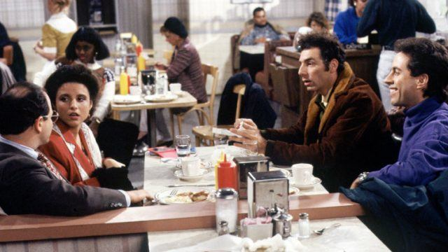 The cast of Seinfeld sitting at a diner together.