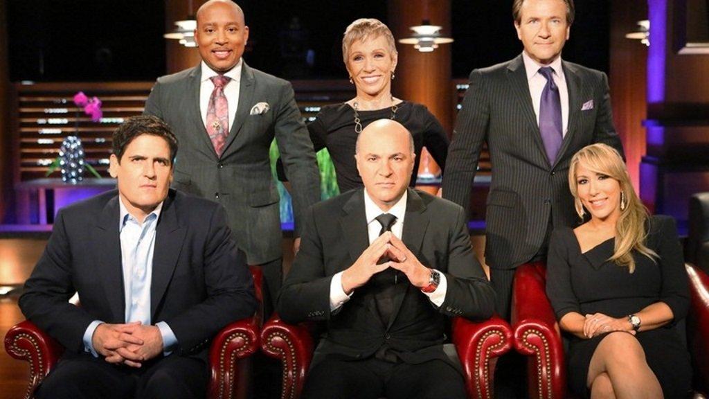 The cast of Shark Tank pose on set