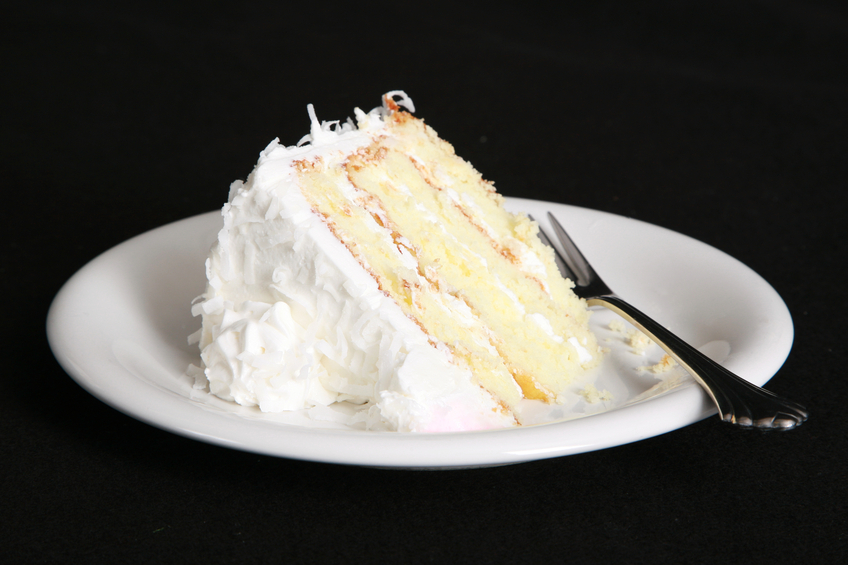 Slice of coconut cake with fork in a plate