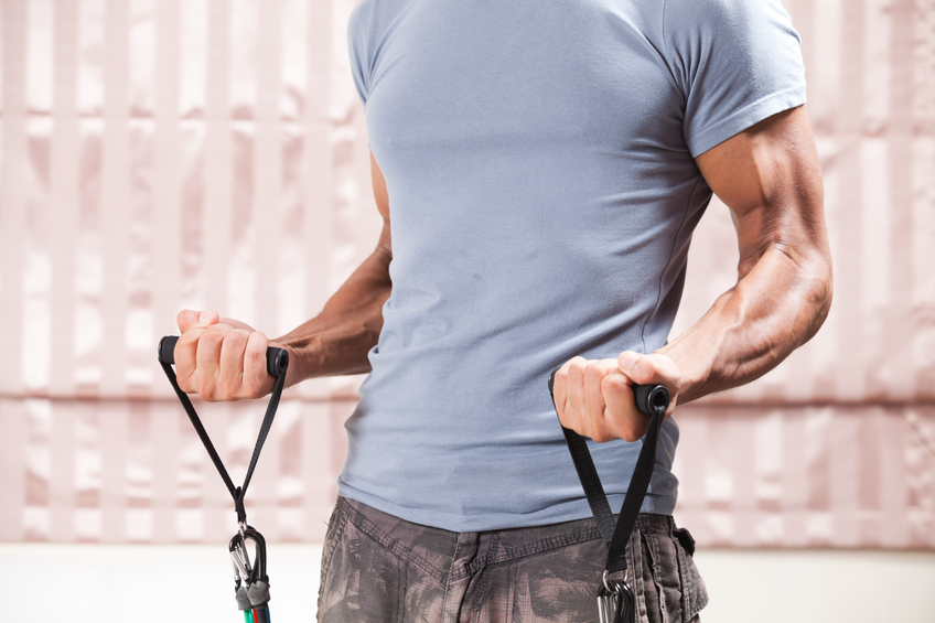 Muscular male using resistance bands