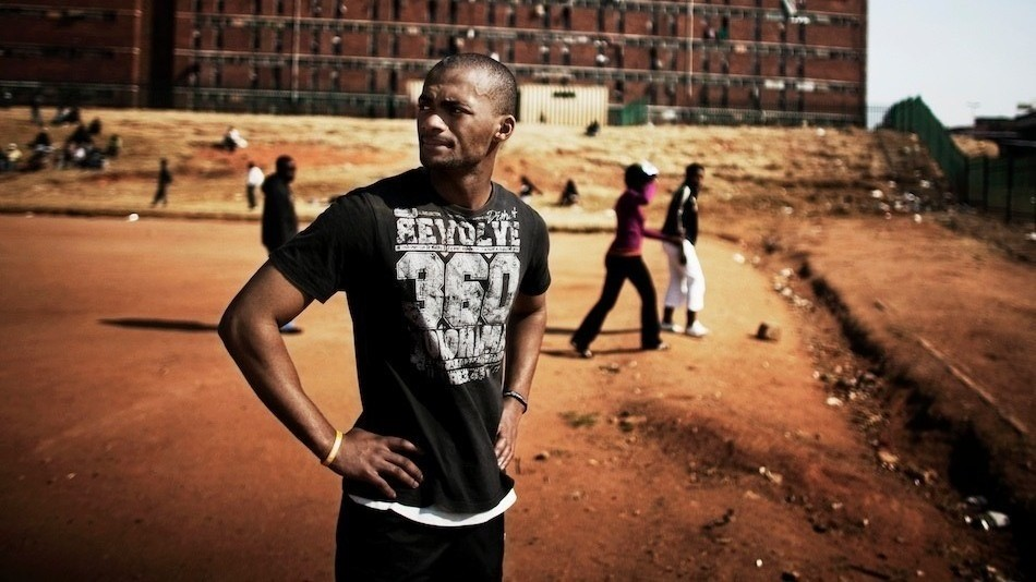 Man standing on a dirt field in Soccer City