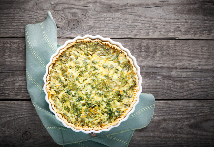 overhead shot of a spinach quiche on a wooden table