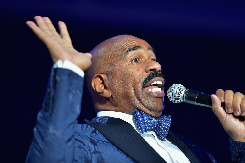 Steve Harvey holds his hands up and speaks into a microphone