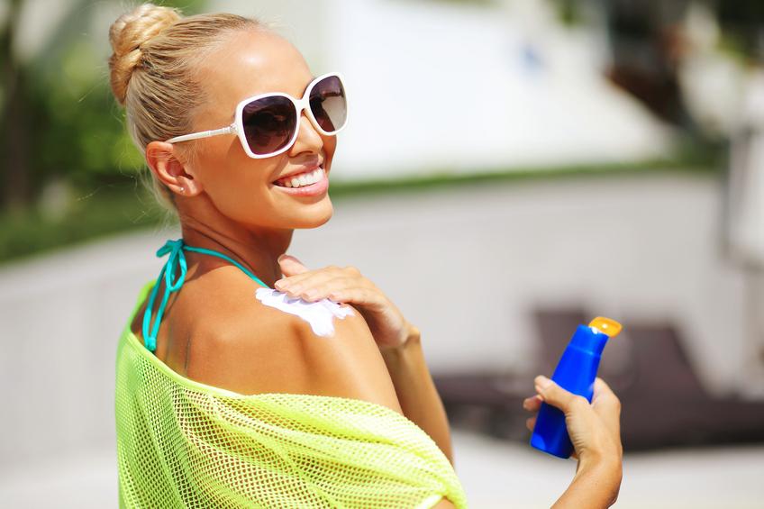 woman applying sun protection lotion
