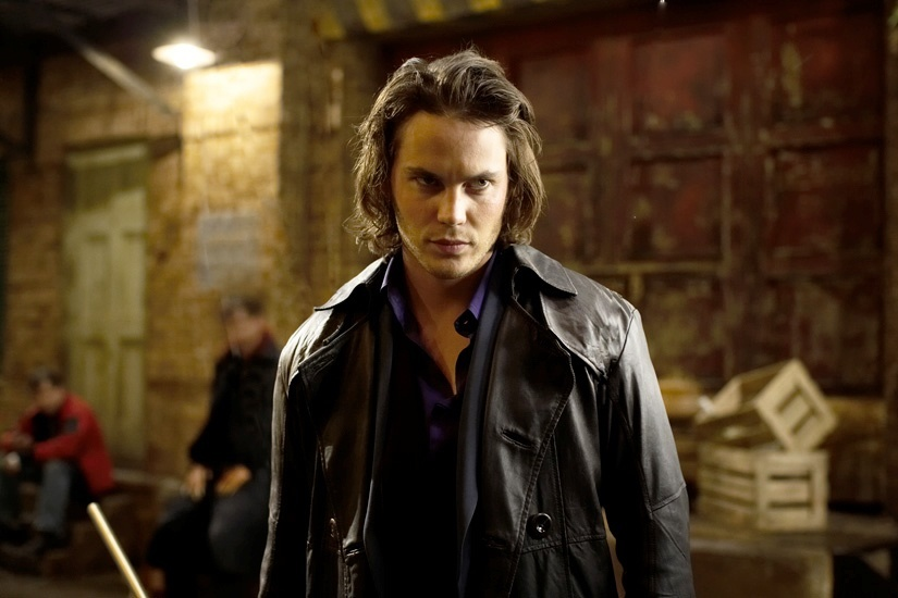 Taylor Kitsch as Gambit, wearing a leather jacket, and holding a pool cue, looking angrily off to the right of the frame