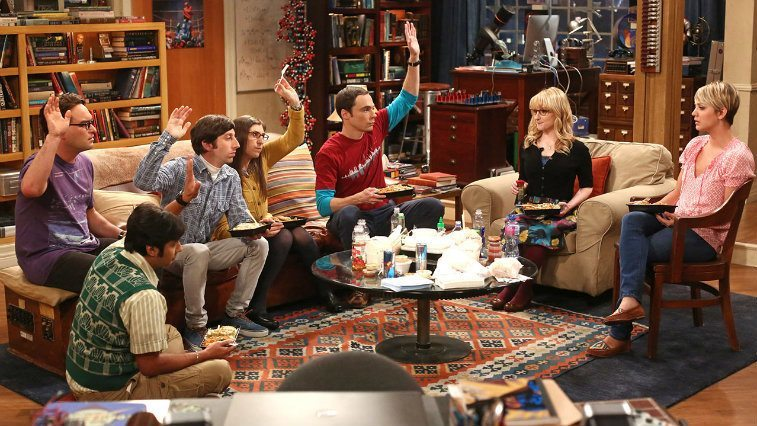 The cast of The Big Bang Theory sit around a table