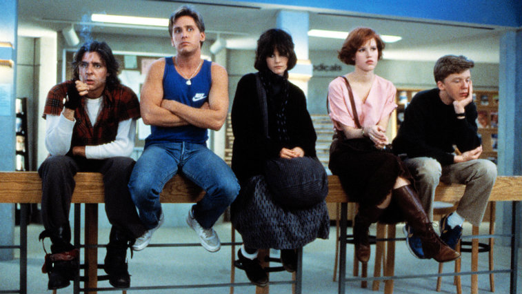 The Breakfast Club cast sitting in the library looking bored