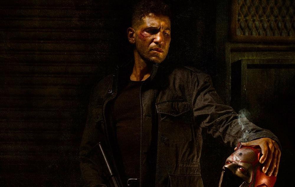 The Punisher glowering, while holding out Daredevil's cowl