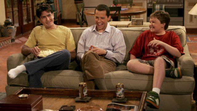 The cast of 'Two and a Half Men' sitting together on a couch as they laugh and watch television.
