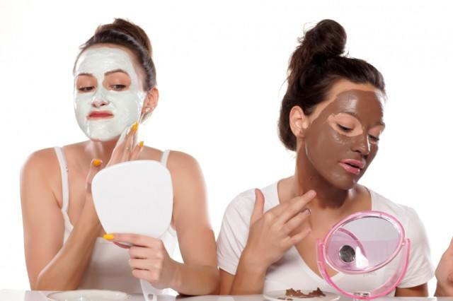 young women appliying face masks in front of mirrors