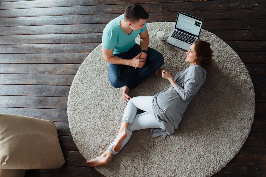 couple lying on carpet with laptop