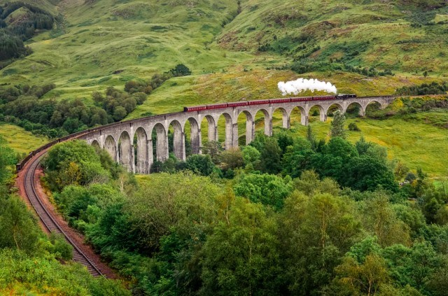 Jacobite steam train traveling across a viaduct in Scotland