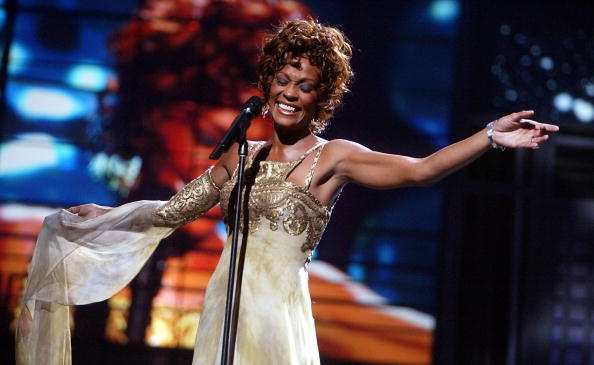 Whitney Houston performing on stage.