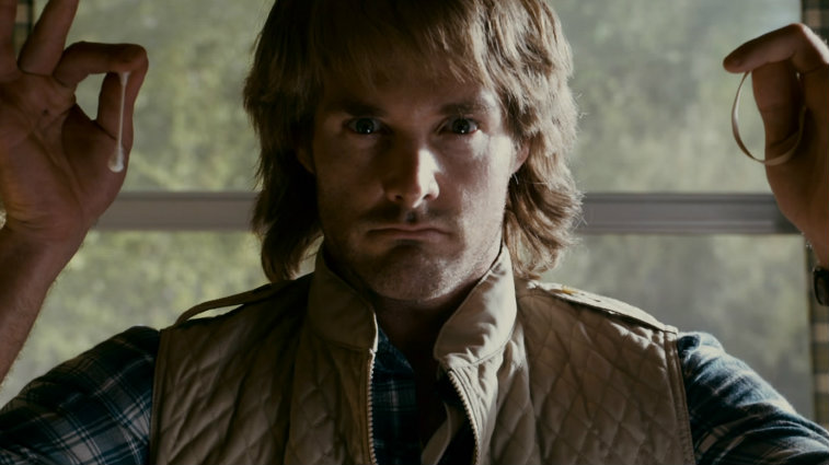 Will Forte holds up a q-tip and a rubber band in each hand in a scene from MacGruber