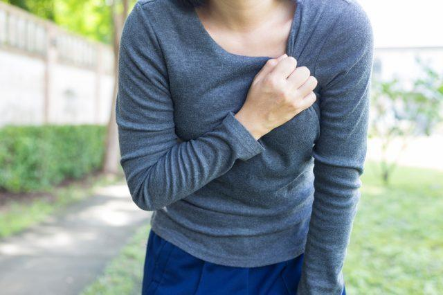 woman clutching her chest while walking outside