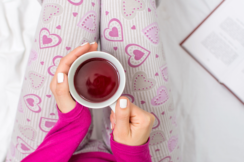 overhead image of a woman's hands holding a cup of tea in bed