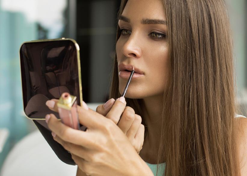Woman putting lipstick