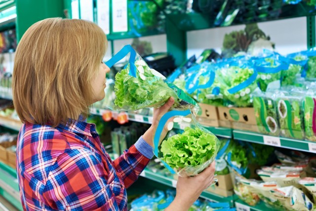 Woman smelling lettuce in grocery store