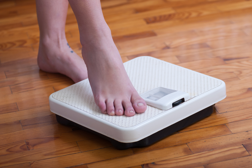 Woman stepping onto a bathroom scale before starting a diet