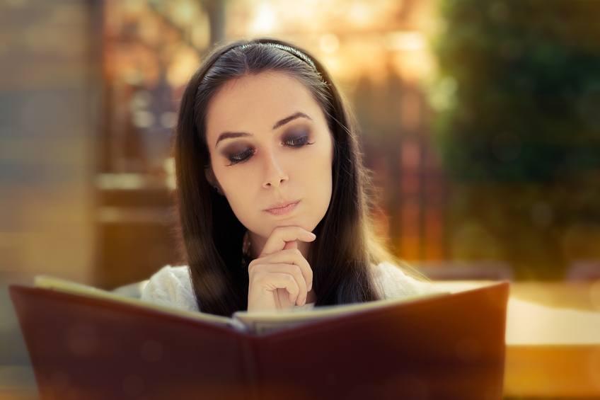 Young Woman reading restuarant menu