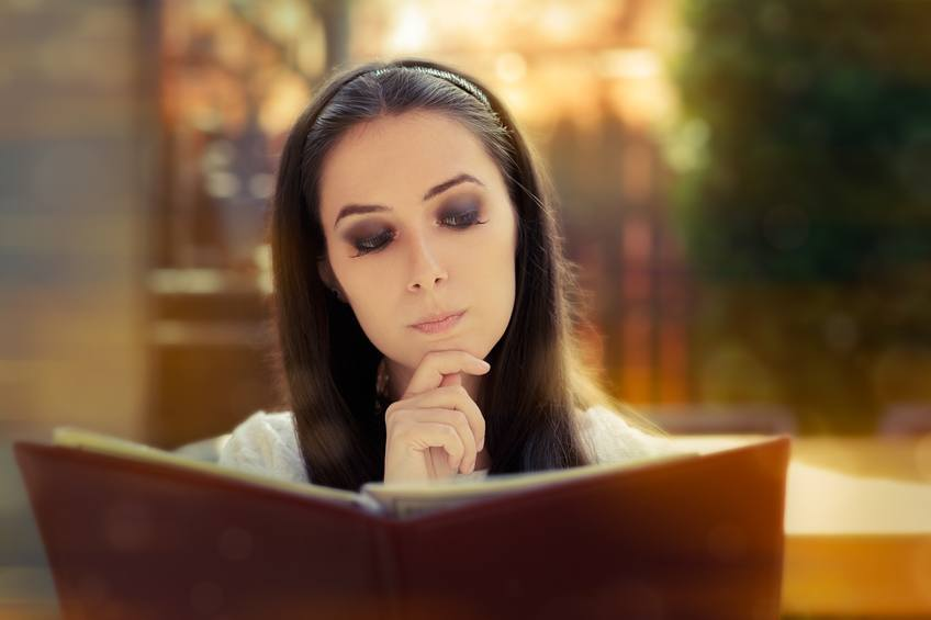 Young woman reading restaurant menu