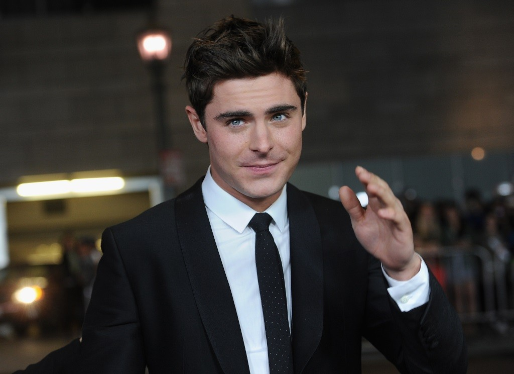 Zac Efron is smiling in a black suit on the red carpet.