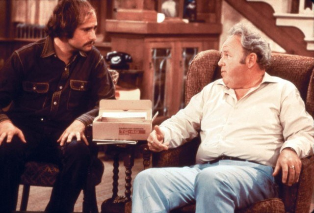 Archie sitting on an armchair while talking to Michael.