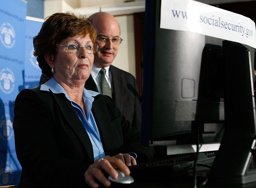 A woman files for her Social Security retirement benefits online as Michael Astrue (R) commissioner of the Social Security Administration stands nearby during a news conference