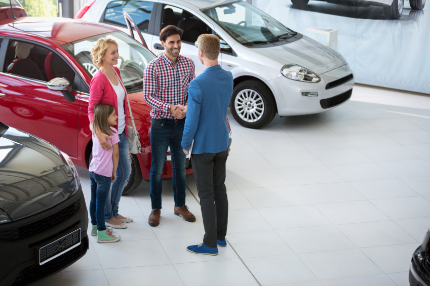 A car salesman congratulates the family in a car showroom