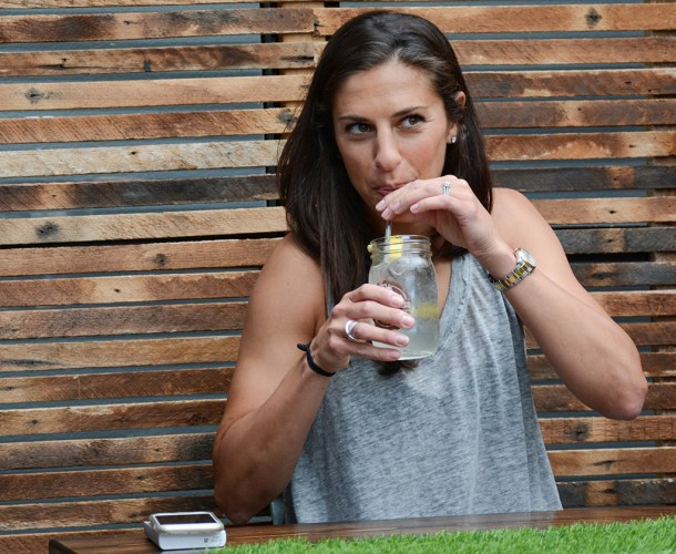 Carli Lloyd sips a glass of water at a Heineken event promoting their soccer campaign