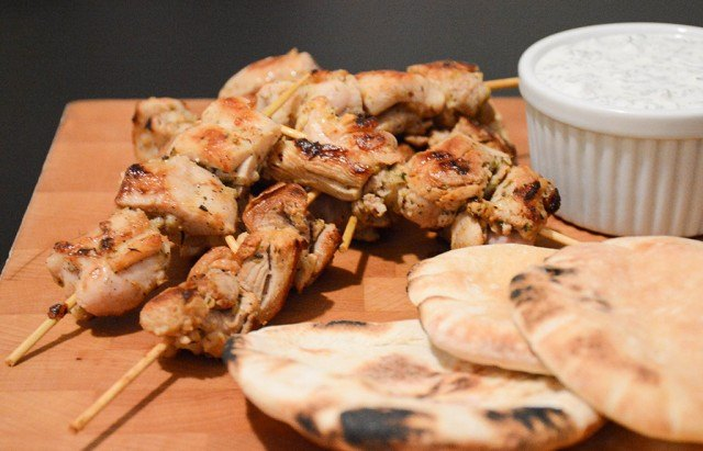 close-up of chicken souvlaki skewers with pita