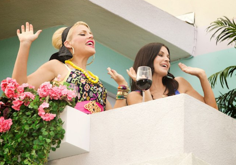 Busy Philipps and Courteney Cox on a white balcony with their hands in the air