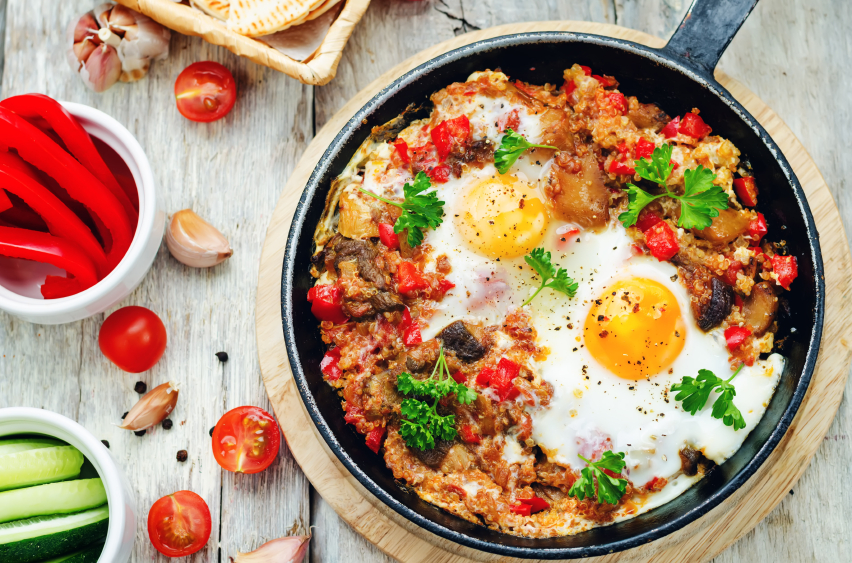 breakfast skillet with quinoa, tomatatoes, peppers, and eggs