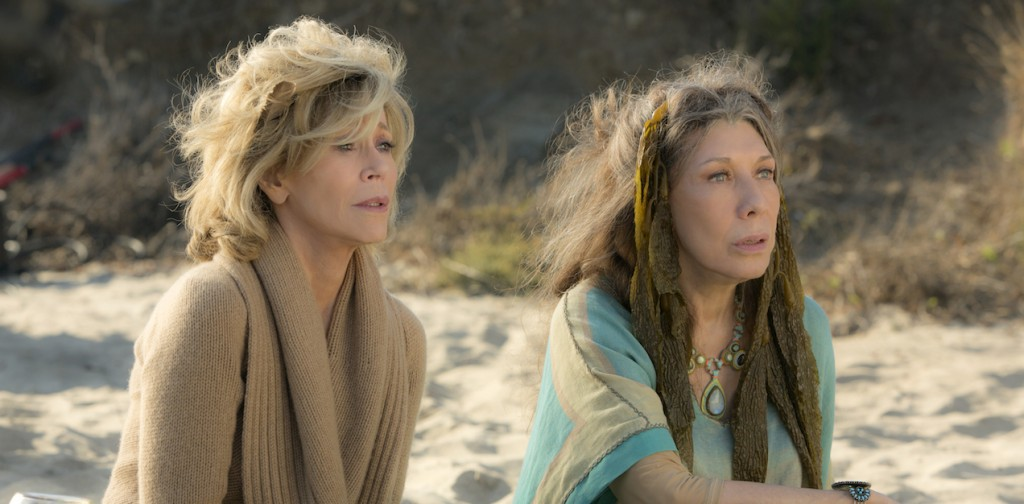 Grace and Frankie sit on a beach looking shocked