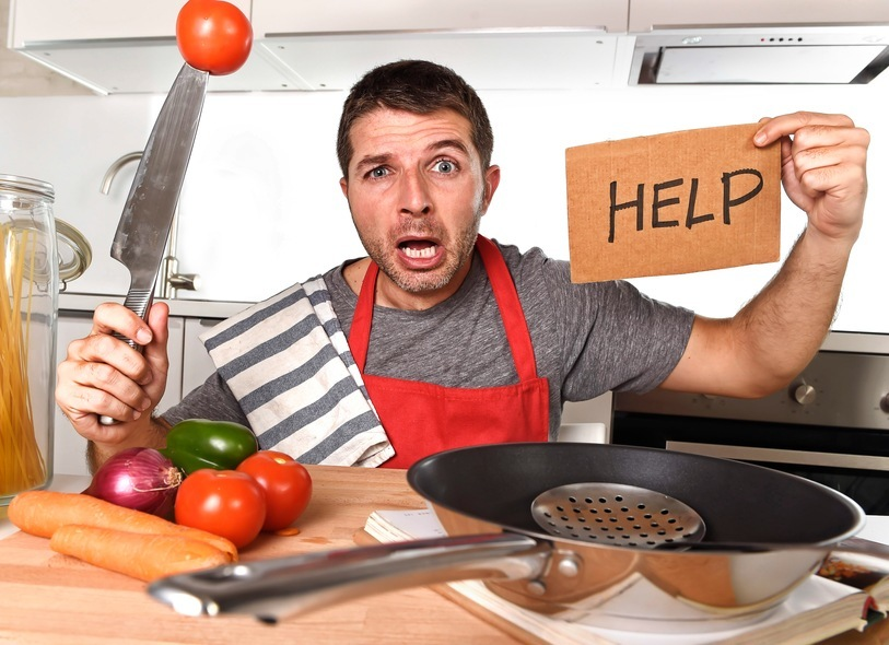 young terrified man at home kitchen wearing cook apron showing help sign looking desperate in stress holding knife with tomato in domestic mess cooking concept