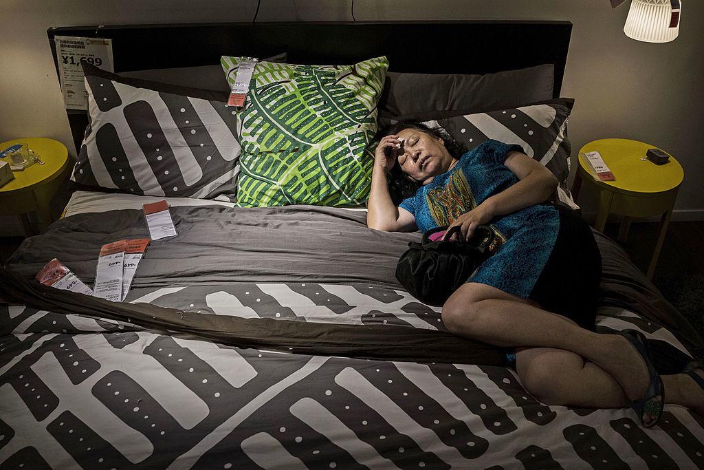 a woman sleeping on an ikea bed